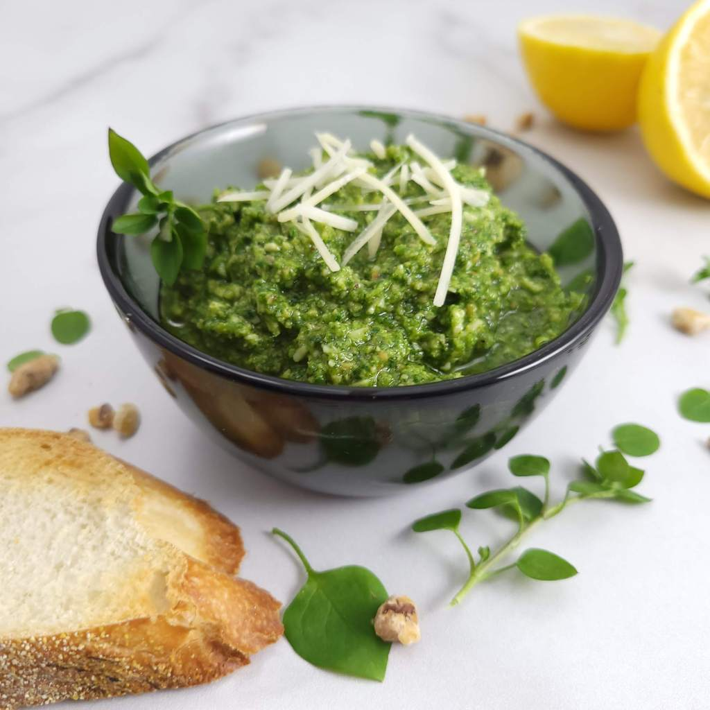 A bowl of chickweed pesto with toast and lemon halves